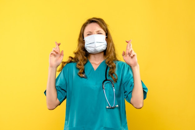 Front view young female doctor hoping in mask on yellow space