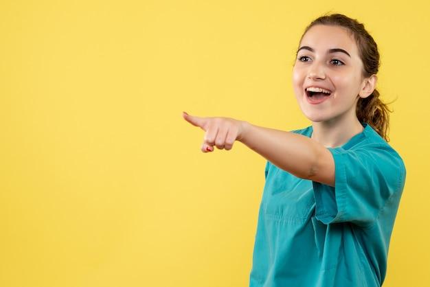 노란색 배경에 의료 소송에서 전면보기 젊은 여성 의사