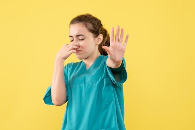 黄色の背景に医療スーツを着た若い女性医師の正面図