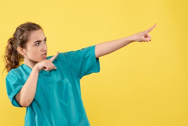 Вид спереди молодая женщина-врач в медицинском костюме на желтом фоне