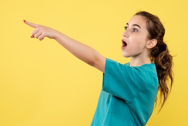 黄色の背景にショックを受けた顔で指している医療スーツの若い女性医師の正面図