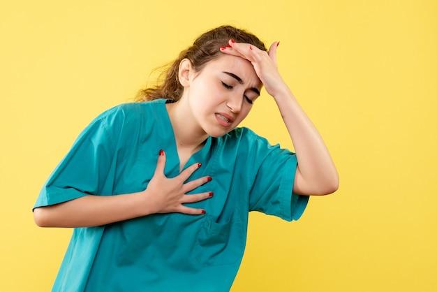 黄色の背景に頭痛のある医療スーツの若い女性医師の正面図