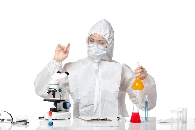 白い背景のスプラッシュパンデミックコビッドウイルスに黄色の溶液を保持しているコビッドのためにマスクと防護服を着た若い女性医師の正面図