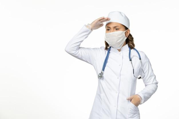 白い医療スーツと白い机の上のコロナウイルスによるマスクと正面図若い女性医師