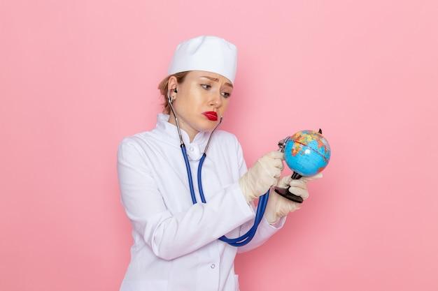 Вид спереди молодая женщина-врач в белом медицинском костюме с синим стетоскопом, проверяющая маленький глобус на розовой космической медицине в медицинской больнице