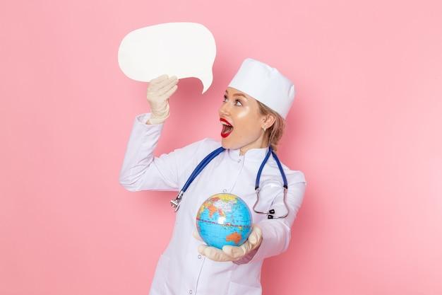 ピンクの宇宙医学医療病院の健康の仕事にグローブと白のサインを保持している青い聴診器で白い医療スーツの正面若い女医