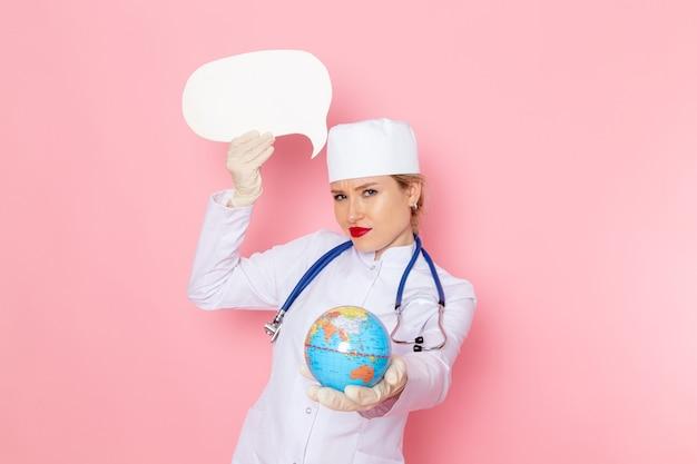ピンクの宇宙医学病院の健康にグローブと白のサインを保持している青い聴診器で白い医療スーツの正面若い女医