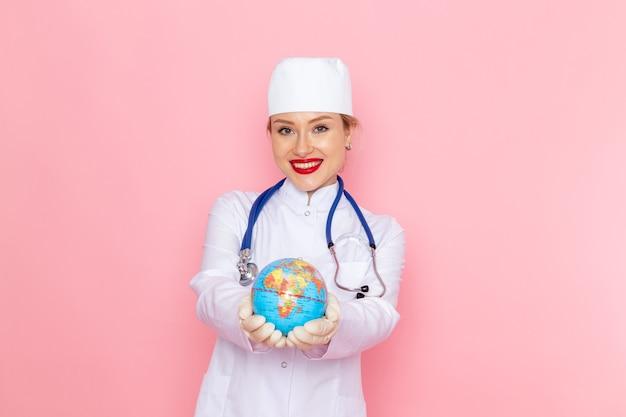 ピンクの宇宙医学医療病院の健康の仕事に笑顔でグローブを保持している青い聴診器で白い医療スーツの正面若い女医