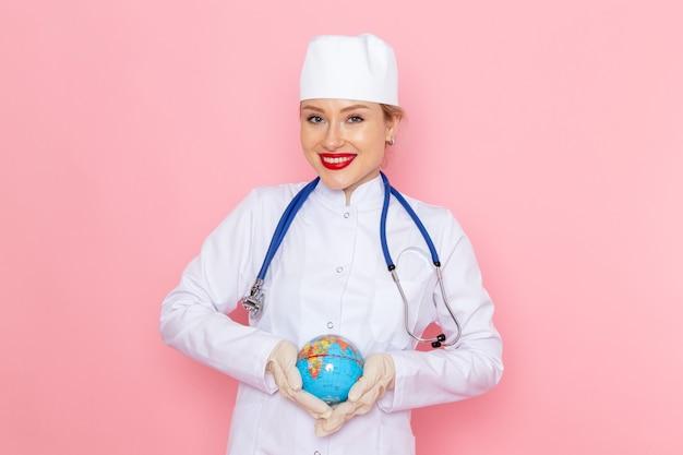 ピンクの宇宙医学医療病院の健康に笑顔でグローブを保持している青い聴診器で白い医療スーツの正面若い女医