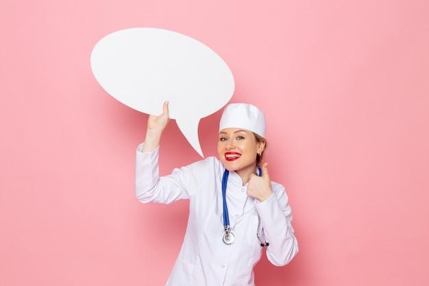 ピンクのスペースに笑顔で巨大な白い看板を持っている青い聴診器で白い医療スーツで正面若い女医