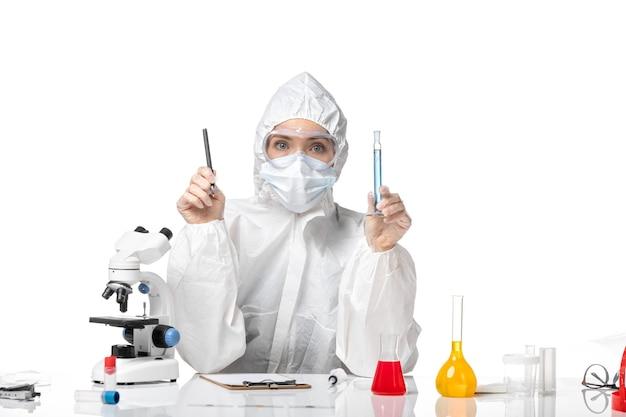 흰색 배경 스플래시 유행성 covid- 바이러스에 파란색 솔루션을 들고 covid로 인해 마스크와 흰색 보호 복에 전면보기 젊은 여성 의사