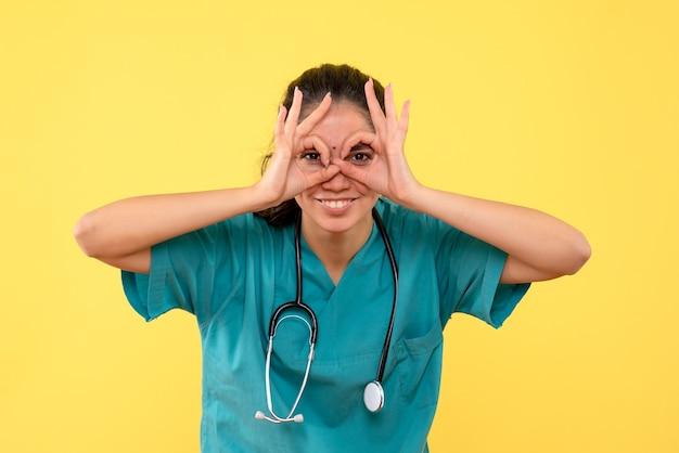 Vista frontale del giovane medico femminile che fa il binocolo a mano sulla parete gialla