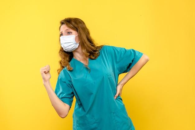 Giovane medico femminile di vista frontale in maschera sullo spazio giallo chiaro