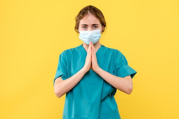 Vista frontale della giovane dottoressa in maschera che prega