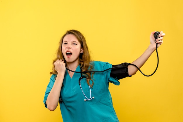 Front view young female doctor measuring pressure on yellow space