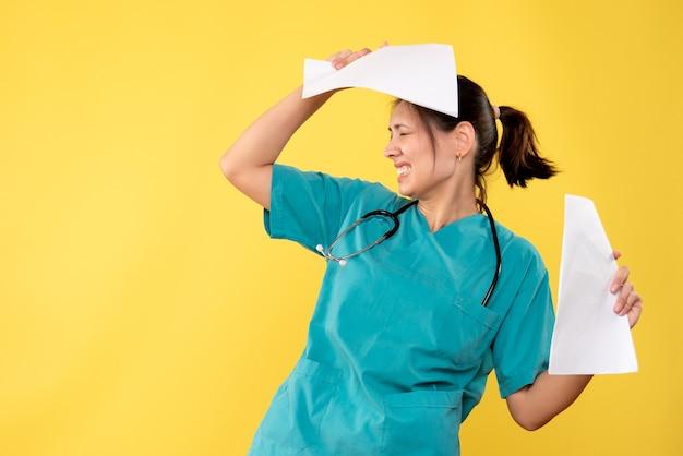 Giovane medico femminile di vista frontale in camicia medica che tiene analisi della carta su fondo giallo