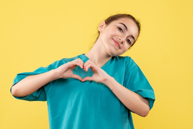 Front view of young female doctor in medical shirt sending love on yellow wall