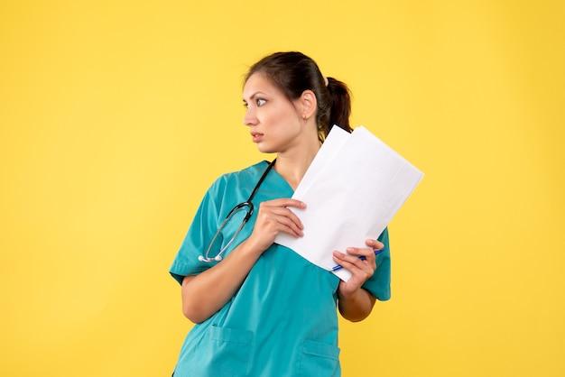 Vista frontale giovane medico femminile in camicia medica con documenti su sfondo giallo