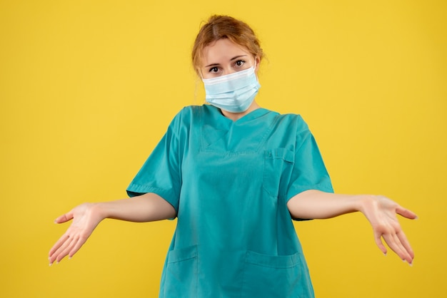 Front view of young female doctor in medical suit and mask on a yellow wall