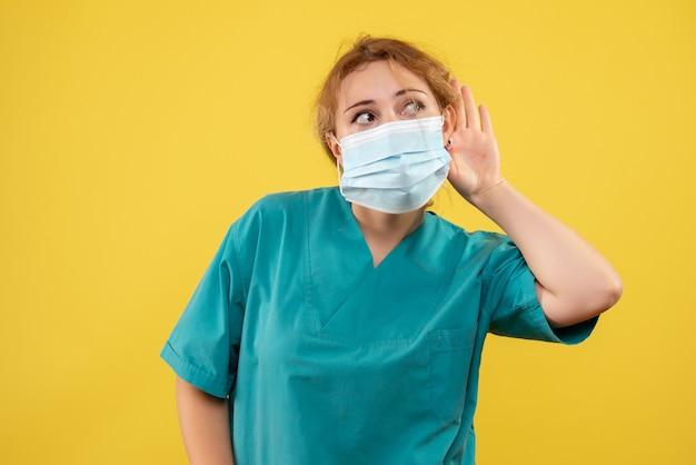 Vista frontale del giovane medico femminile in tuta medica e maschera sulla parete gialla