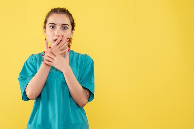 Giovane medico femminile di vista frontale in vestito medico su priorità bassa gialla