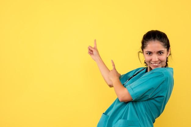 Vista frontale del giovane medico femminile che punta a dietro sulla parete gialla