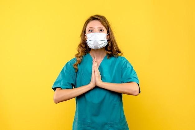 Giovane medico femminile di vista frontale che prega nella mascherina sullo spazio giallo