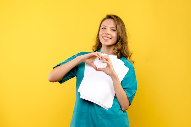 Front view young female doctor sending love on yellow space