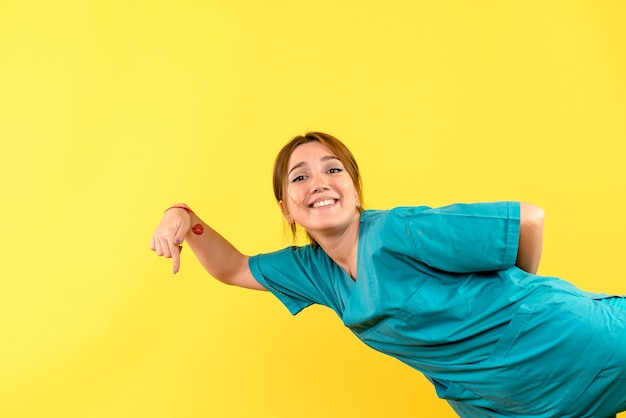Front view of young female doctor smiling on yellow wall