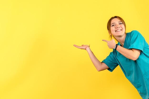 Vista frontale del giovane medico femminile che sorride sulla parete gialla