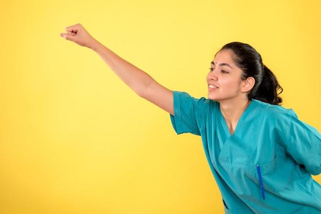 Vista frontale della giovane dottoressa in posa super eroe sulla parete gialla
