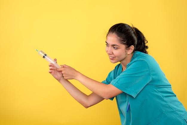 Vista frontale della giovane donna medico utilizzando la siringa sulla parete gialla