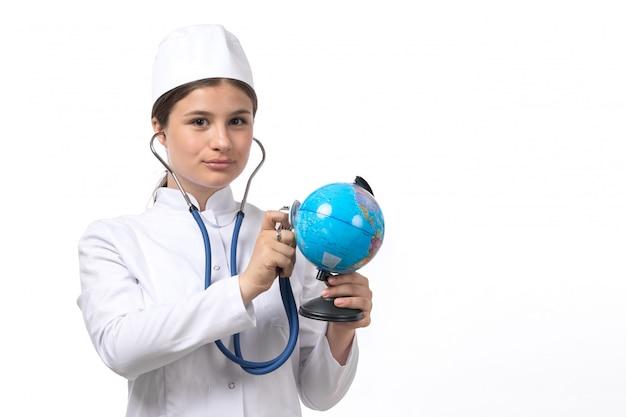 Una giovane dottoressa vista frontale in tuta medica bianca con stetoscopio blu controllando il globo