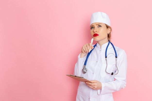 Front view young female doctor in white medical suit with blue stethoscope holding notepad and thinking on the pink space