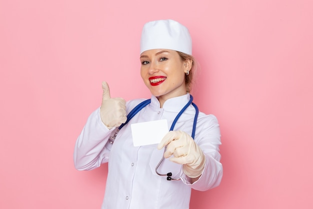 Front view young female doctor in white medical suit with blue stethoscope holding white card smiling on the pink space