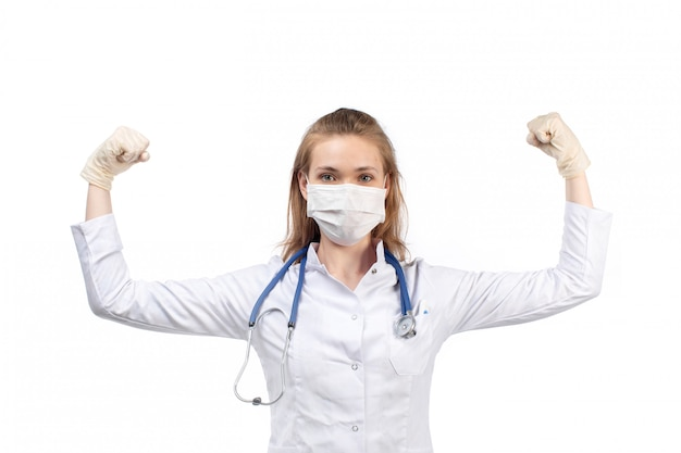 A front view young female doctor in white medical suit with stethoscope wearing white protective mask in gloves flexing on the white