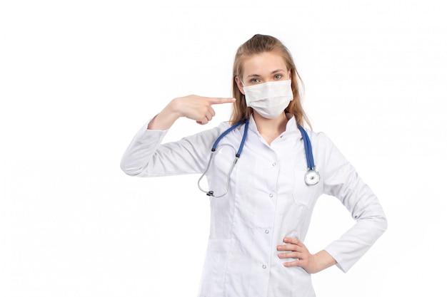 Un giovane medico femminile di vista frontale in vestito medico bianco con lo stetoscopio che indossa maschera protettiva bianca che posa sul bianco