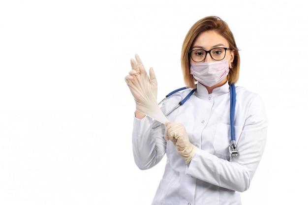 Una giovane dottoressa in vista frontale bianco vestito medico con stetoscopio indossando guanti protettivi maschera bianca sul bianco
