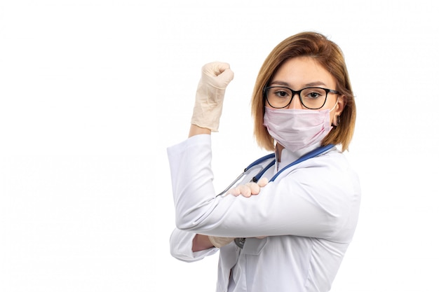A front view young female doctor in white medical suit with stethoscope wearing white protective mask wearing gloves on the white