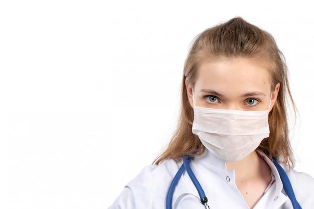 Un giovane medico femminile di vista frontale in vestito medico bianco con lo stetoscopio che indossa maschera protettiva bianca sul bianco