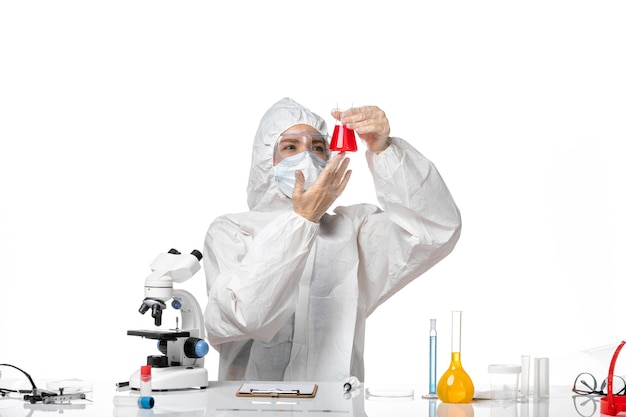 Front view young female doctor in white protective suit with mask due to covid holding red solution on a white desk virus pandemic splash covid-