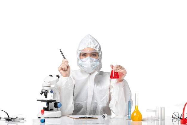 Front view young female doctor in white protective suit with mask due to covid holding red solution on the white floor virus pandemic splash covid-