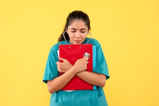 Vista frontale della giovane dottoressa con documenti sulla parete gialla