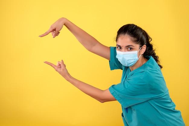 Vista frontale del giovane medico femminile con la maschera sulla parete gialla