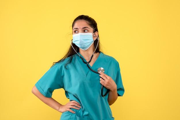 Vista frontale del giovane medico femminile con la mascherina medica che tiene lo stetoscopio sulla parete gialla