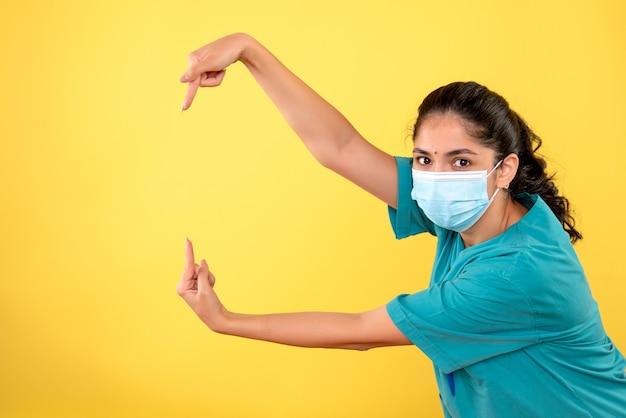 Vista frontale del giovane medico femminile con mascherina medica sulla parete gialla