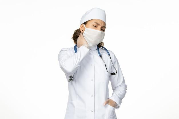 Вид спереди молодая женщина-врач со стерильной маской и перчатками из-за коронавируса с болью в шее на белой поверхности