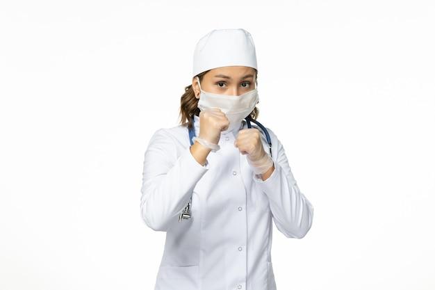 明るい白色の表面にコロナウイルスによる滅菌マスクと手袋を着用した若い女性医師の正面図