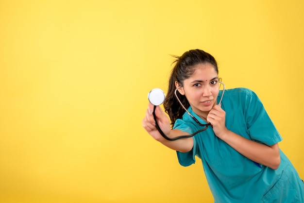 Vista frontale del giovane medico femminile con lo stetoscopio in piedi sulla parete gialla