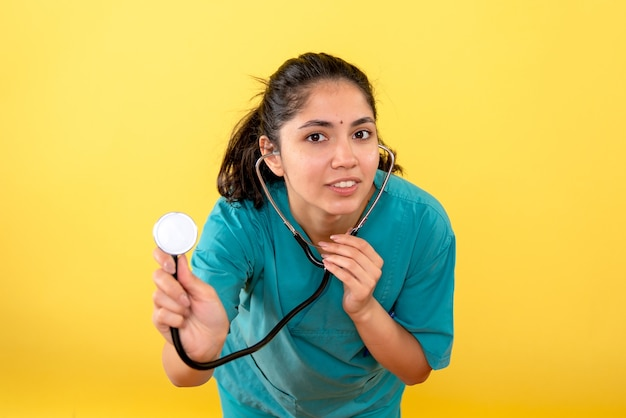 Front view of young female doctor with stethoscope on yellow wall